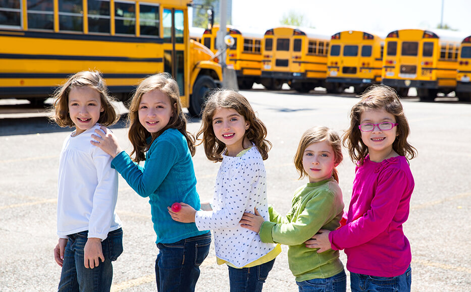 young girls in front of schoolbuses